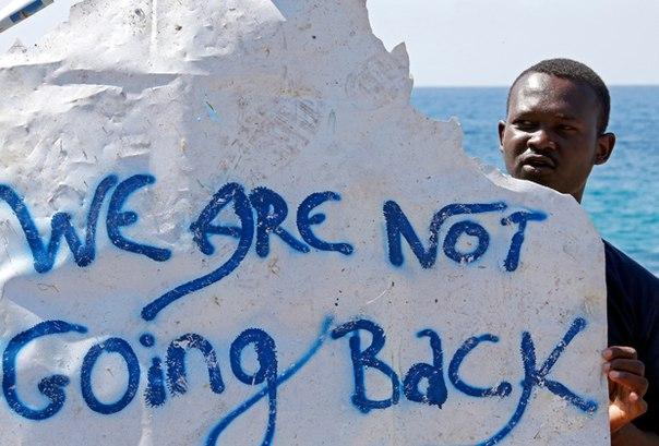 """На фото: африканский беженец с плакатом """"Мы не собираемся обратно"""""""