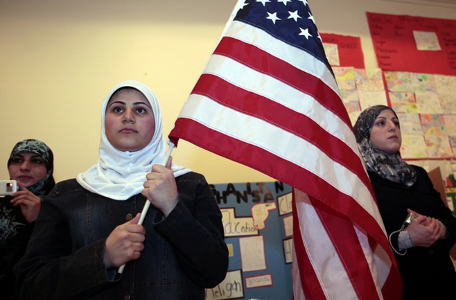 A young Muslim American female student holds the U.S. flag during a 'Children of the World' student pageant at the Islamic Center of America in Dearborn, Michigan, March 26, 2010.  A growing school of thought among counterterrorism specialists, and within the administration of U.S. President Barack Obama, argues that law enforcement should engage more deeply with the Muslim community. Their case has been bolstered by encouraging examples of outreach programs. Picture taken March 26. To match SPECIAL REPORT USA-SECURITY/HOMEGROWN  REUTERS/Rebecca Cook  (UNITED STATES - Tags: RELIGION POLITICS)
