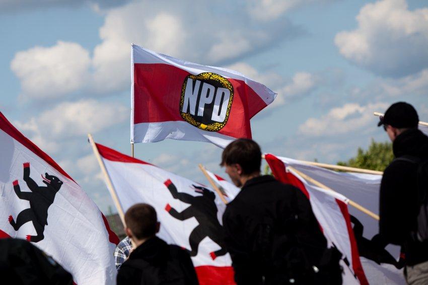Teilnehmer einer NPD-Kundgebung zum 50. Jahrestag des Mauerbaus stehen am Samstag (13.08.11) in Berlin mit einer NPD-Fahne auf der Boesebruecke. Begleitet von einem grossen Aufgebot an Sicherheitskraeften haben nach Polizeiangaben rund 650 Menschen in Prenzlauer Berg gegen die NPD-Kundgebung demonstriert. Etwa 60 Rechtsextreme hatten sich am Samstag am ehemaligen innerstaedtischen Grenzuebergang an der Bornholmer Strasse zu einem Gedenken fuer die Mauertoten versammelt. (zu dapd-Text) Foto: Maja Hitij/dapd