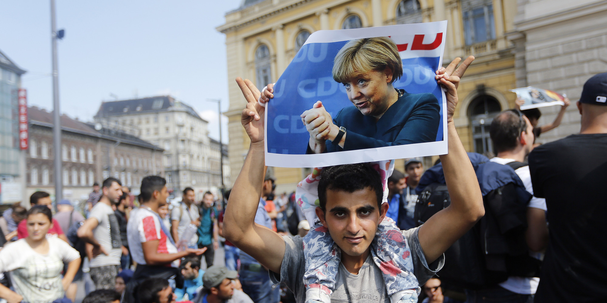 A man holds up a poster of German Chacellor Angela Merkel before starting a march out of  Budapest, Hungary, Friday, Sept. 4, 2015. Over 150,000 people seeking to enter Europe have reached Hungary this year, most coming through the southern border with Serbia, and many apply for asylum but quickly try to leave for richer EU countries. (AP Photo/Frank Augstein)
